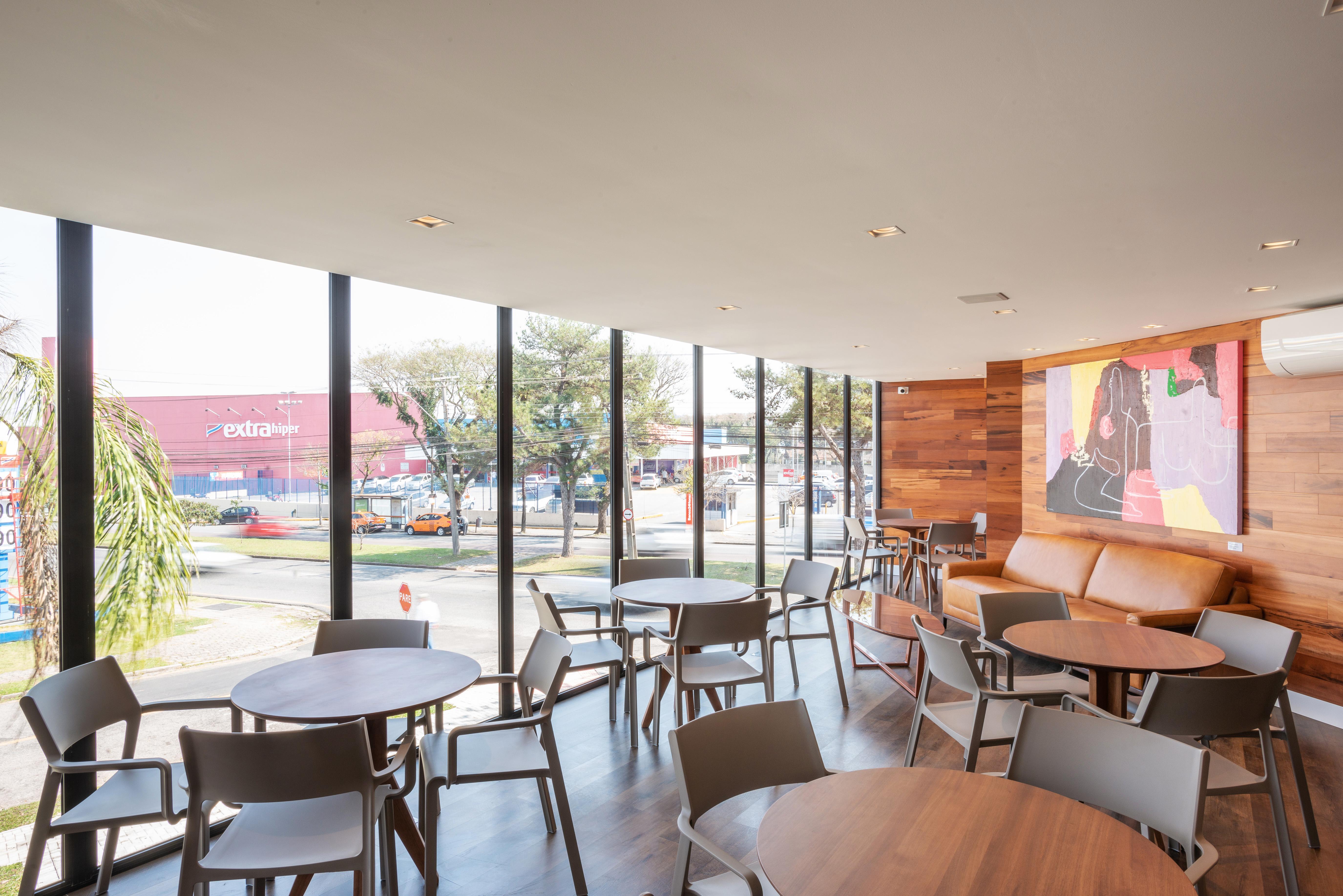 Área gourmet conta com panos de vidro, muita iluminação natural e acabamentos em madeira natural.