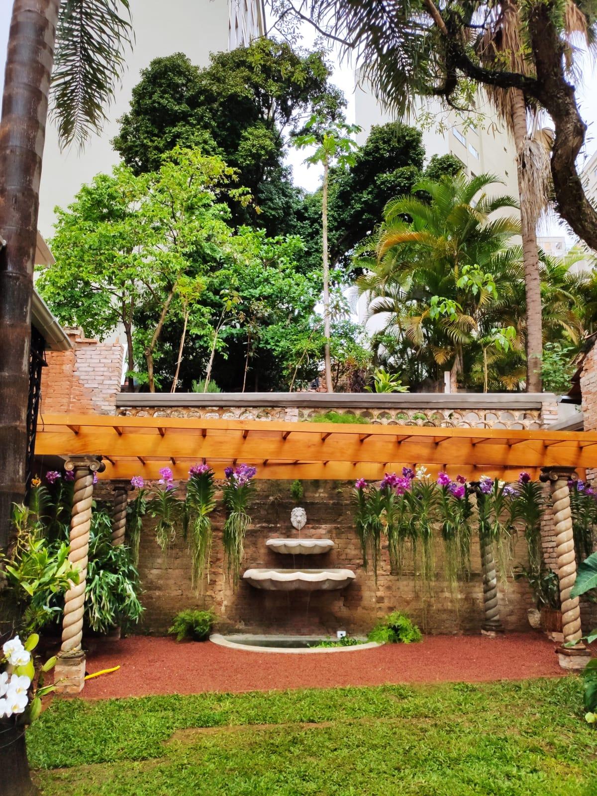 Terreno de 2 mil m² tem orquidário com plantas suspensas e fonte de água.