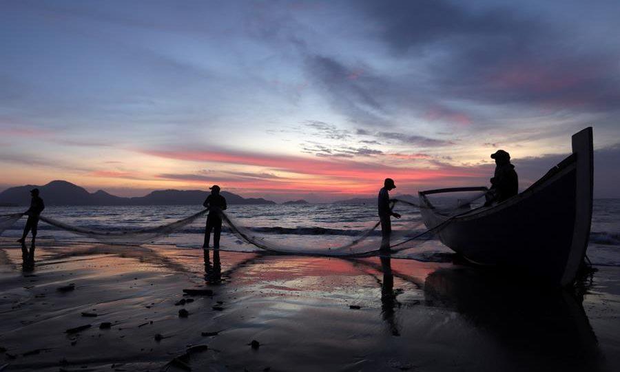 Pescadores tradicionais coletam peixes de uma rede de pesca em Kampung Jawa, em Aceh, Indonésia, setembro de 2019