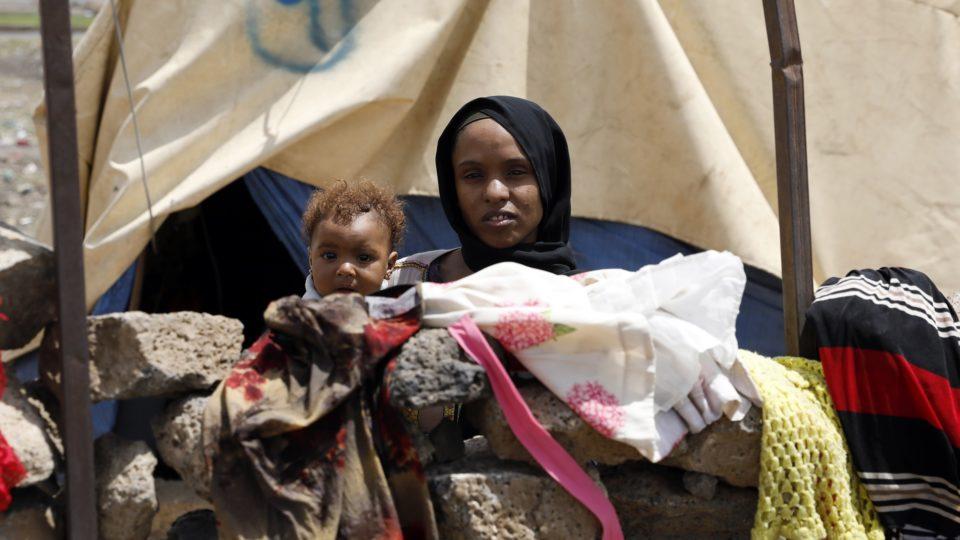 Mãe carrega a filha em campo de refugiados no Iêmen