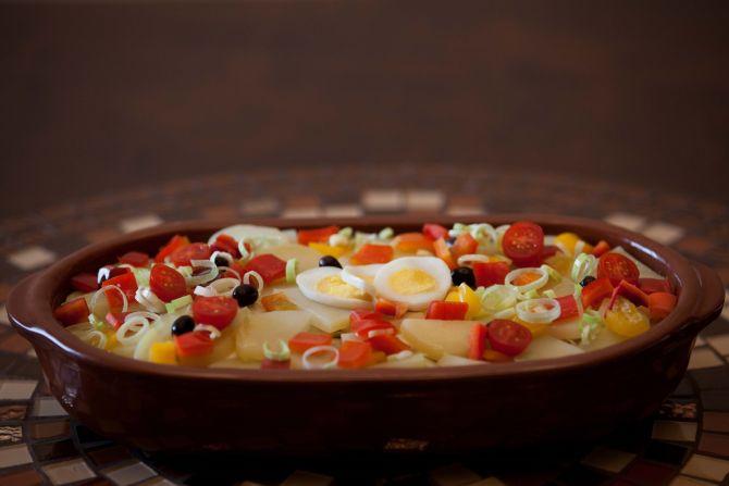 Lombos de bacalhau disposto em camadas com cebolas refogadas, pimentões, tomates cereja, alho poró, azeitonas pretas, ovos cozidos e batatas fatiadas. Foto: Divulgação