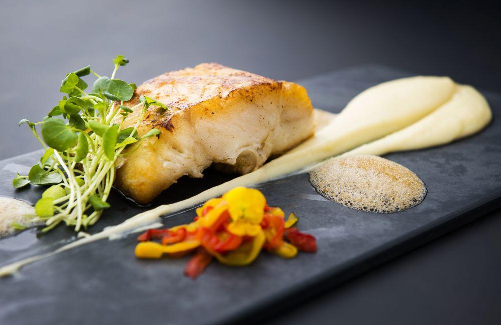 Lombo de bacalhau assado é servido com purê de batata e alho, confit de pimentão e espuma de azeitona preta (R$ 79). (Foto: Letícia Akemi/Gazeta do Povo)