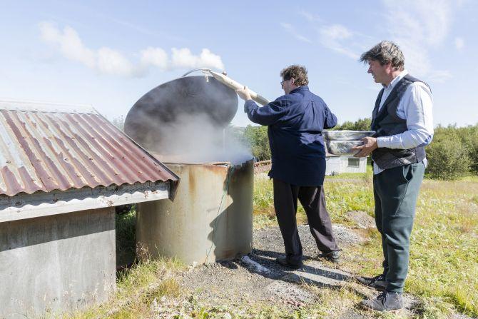 Jon Sigfusson, chef no Fridheimar, e Kjartan Olafsson, um crítico de gastronomia e exportador de peixes, colocam comida dentro de um forno geotermal comunitário. Foto: Bara Kristinsdottir/The New York Times