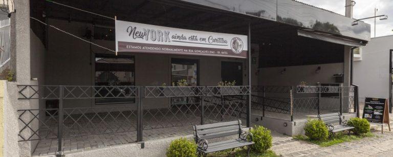 Fachada do NY Café no Alto da XV com uma faixa avisando que a cafeteria continua funcionando no Batel. Foto: Fernando Zequinão/Gazeta do Povo