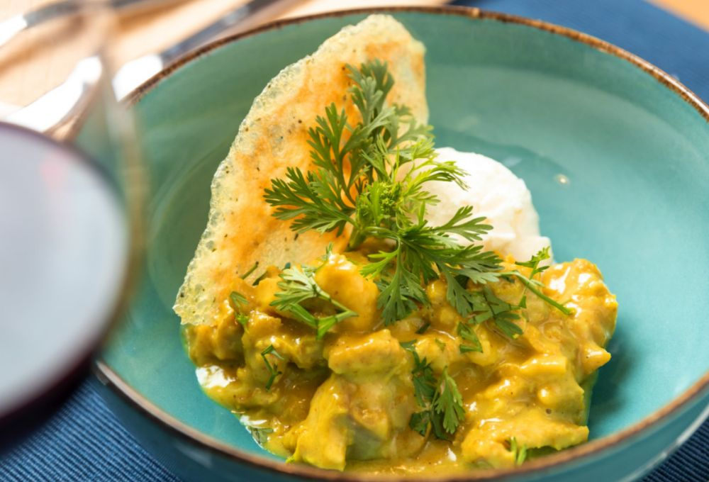 O curry de frango faz um curioso contraste com o sorvete de coco, com o tempero amenizado pelo frescor da fruta. Foto: reprodução Instagram.