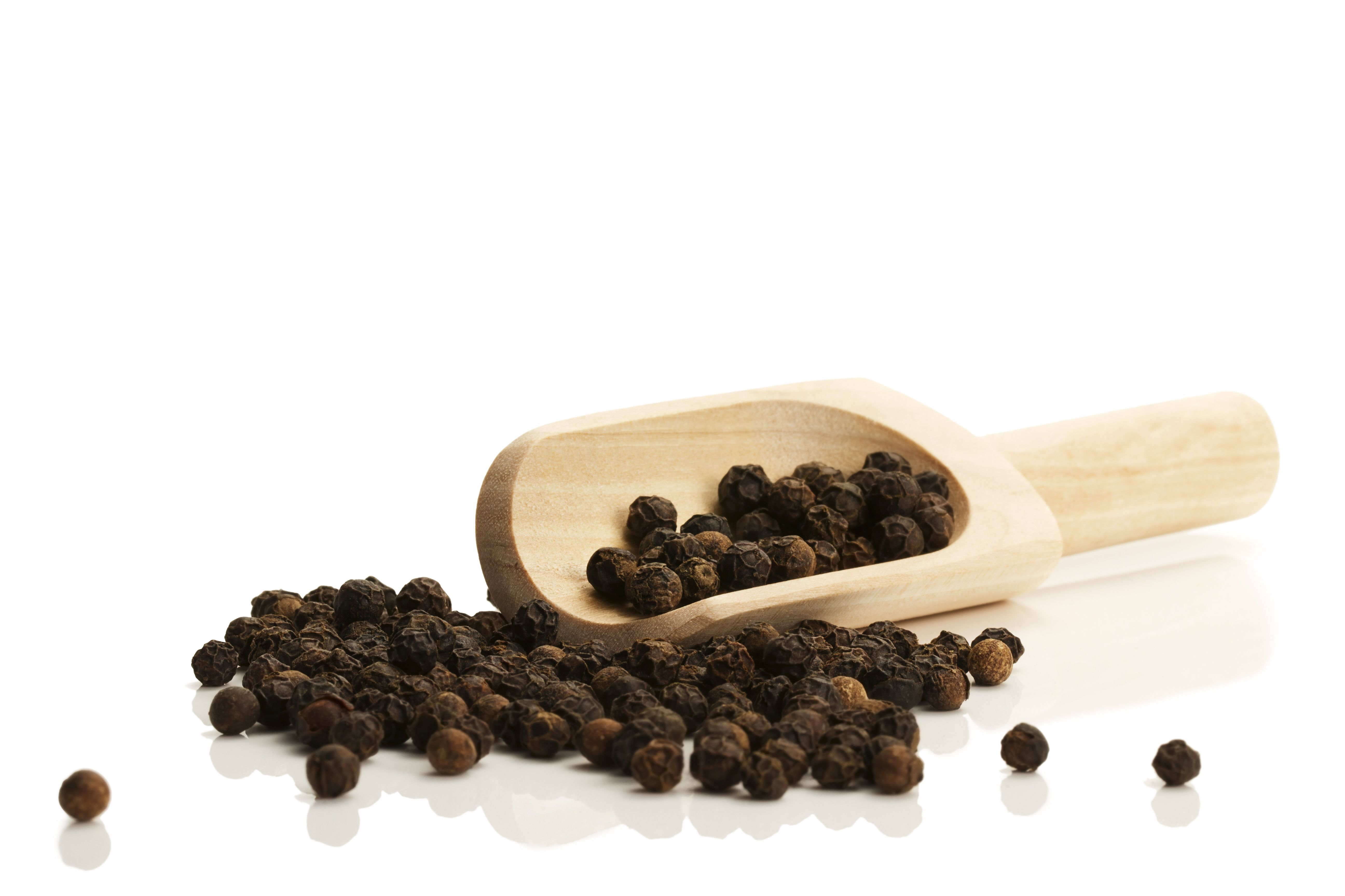 black peppercorns with a small wooden shovel from side on white background