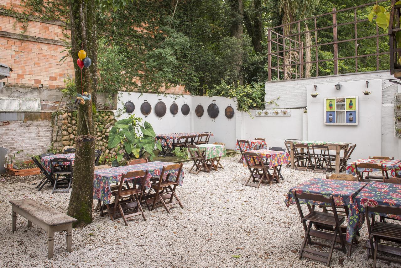 """No quintal, a decoração reutiliza elementos que """"sobreviveram"""" ao incêndio, como o disco de arado, canequinhas de ágata e panelinhas do buffet. Foto: Letícia Akemi/Bom Gourmet"""