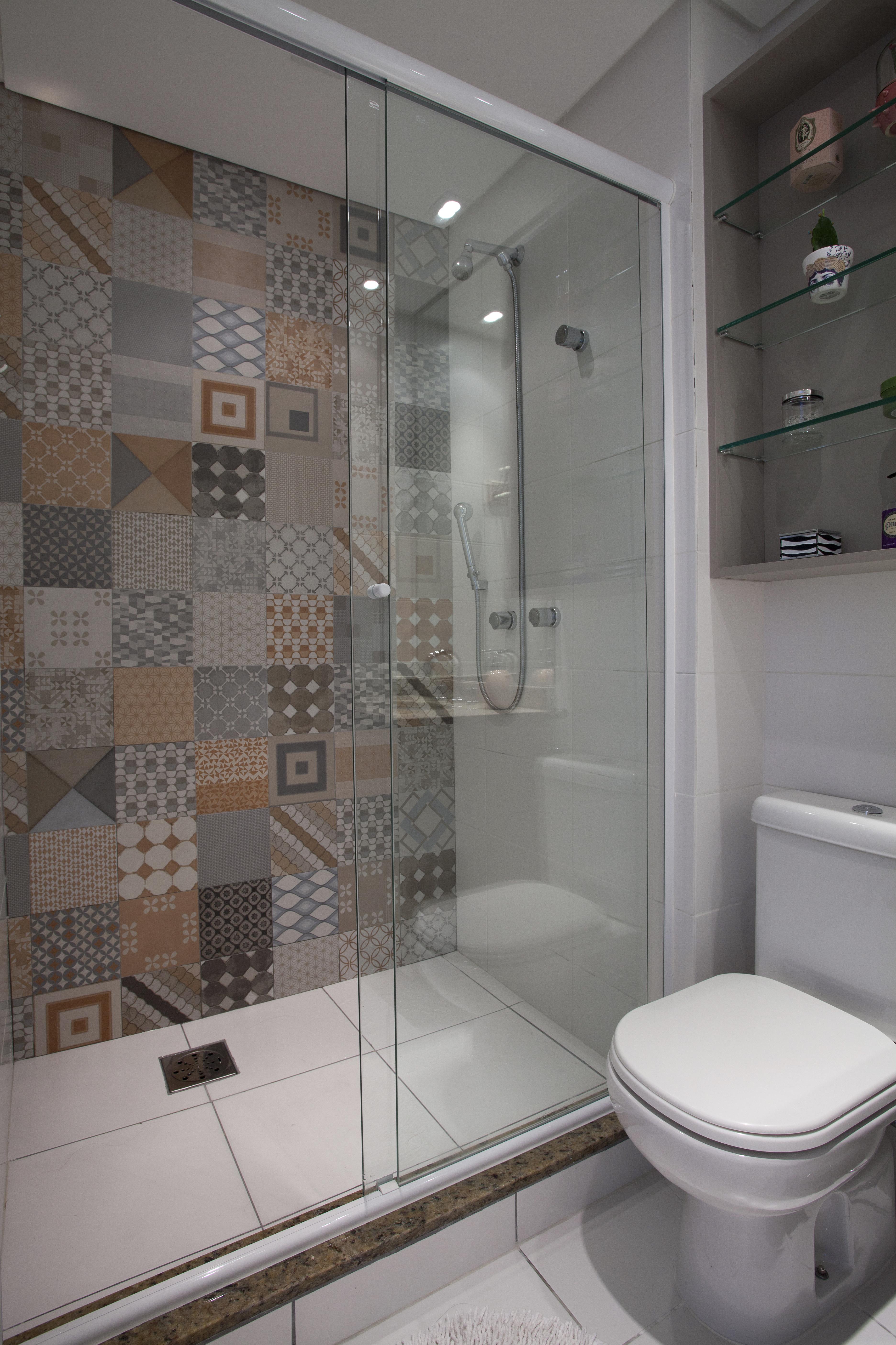 O banheiro não ficou só no branco tradicional. Peças cerâmicas que lembram os ladrilhos hidráulicos foram aplicadas em uma parede inteira.