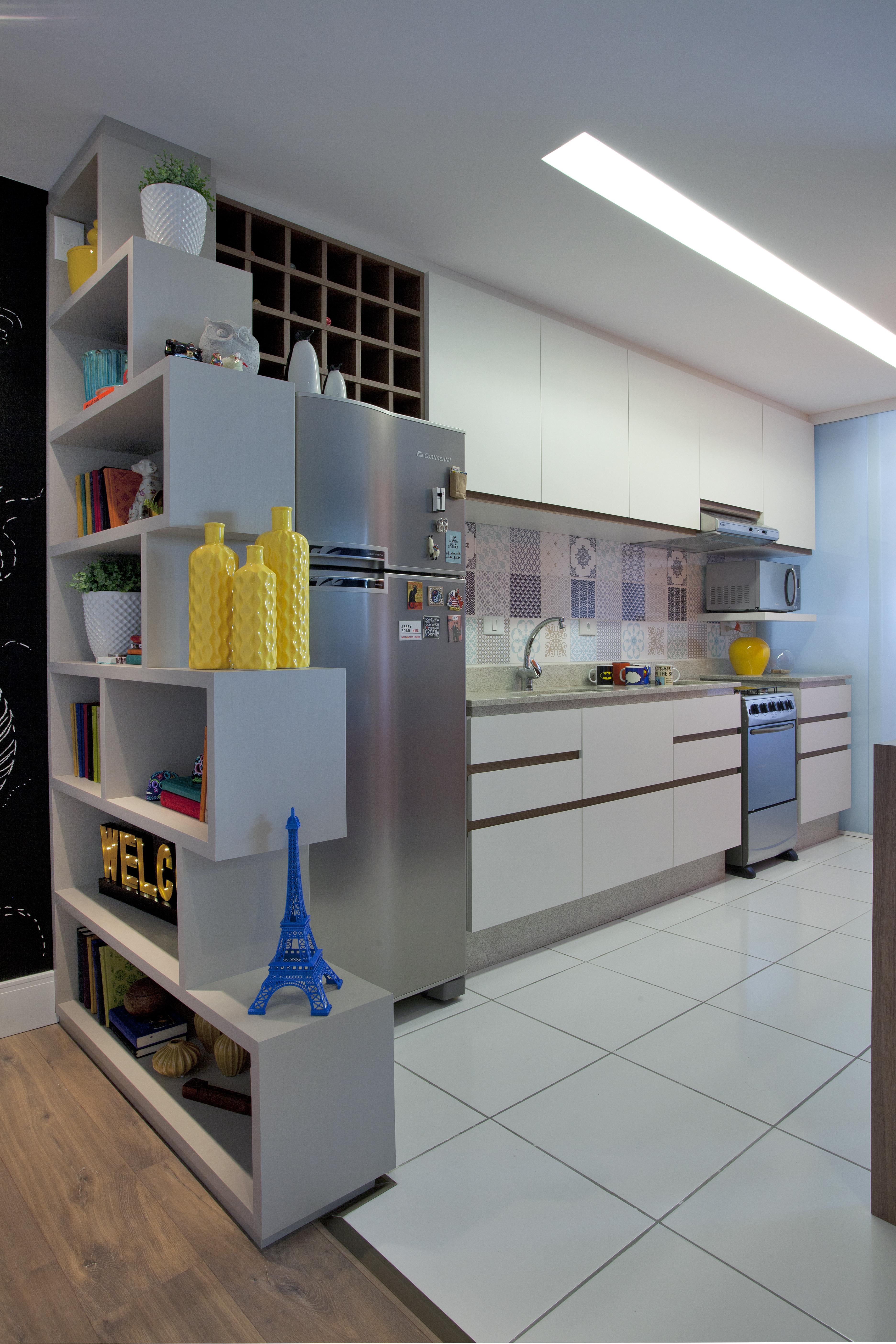 A cozinha é integrada com a área social e  tem cores que conversam com os tons usados na sala.
