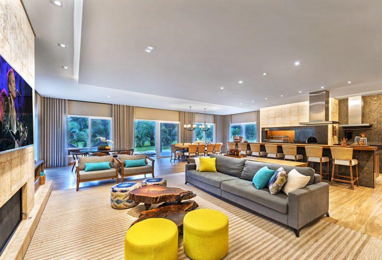 No projeto da NP Arquitetura, alguns elementos de cor dão mais personalidade para a sala de estar. Destaque para a mesa de centro de troncos de árvore.  Foto: Gerson Lima / Divulgação