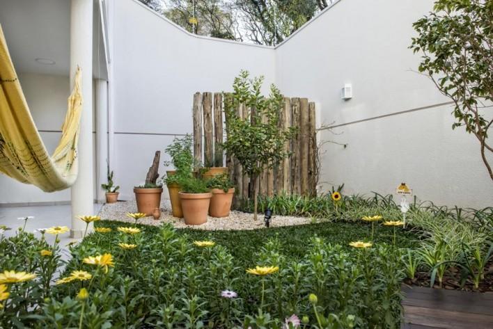 A paisagista Claudia Canales deu alma de interior aos fundos de uma casa com diversas flores e árvores frutíferas