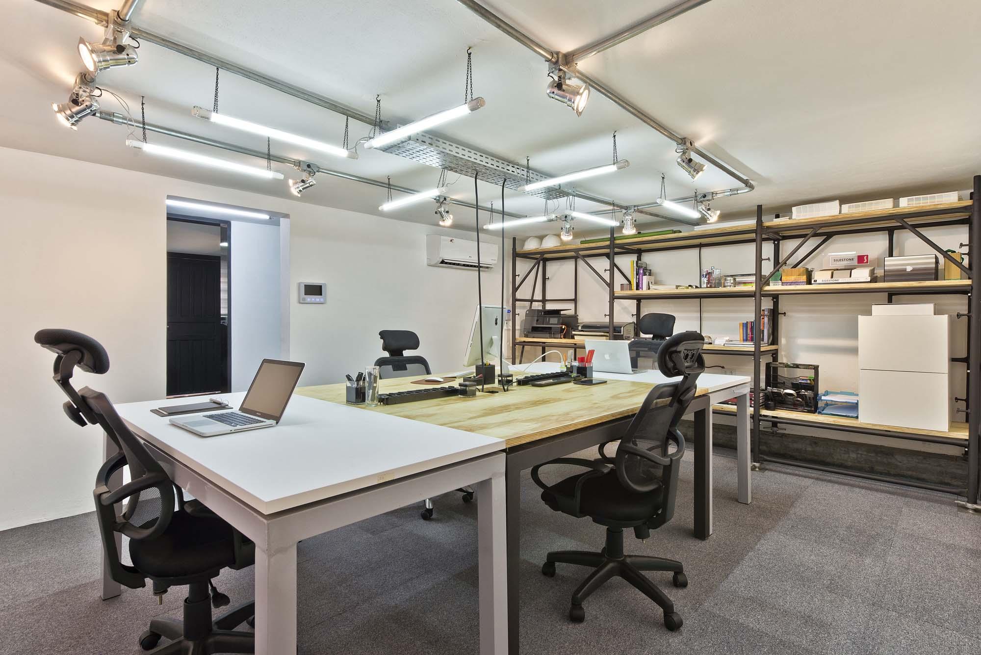 Sala de projetos tem iluminação mais potente para o trabalho. As instalações foram feitas de forma aparente, reforçando a linguagem industrial.