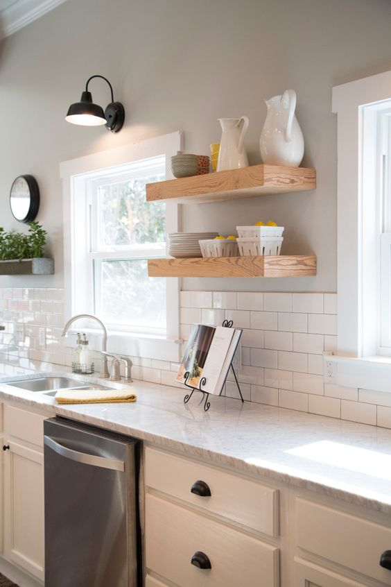 Fixer Upper Hosts Chip and Joanna Gaines have gutted and transformed the kitchen.  They added new Carrera marble countertops, cabinets, floating wood shelves, a subway tile backsplash, and fresh light gray paint.  Stainless appliances and  a stainless sink and faucet are clean and modern, as seen on HGTV's Fixer Upper.  (After 11a)  Afters