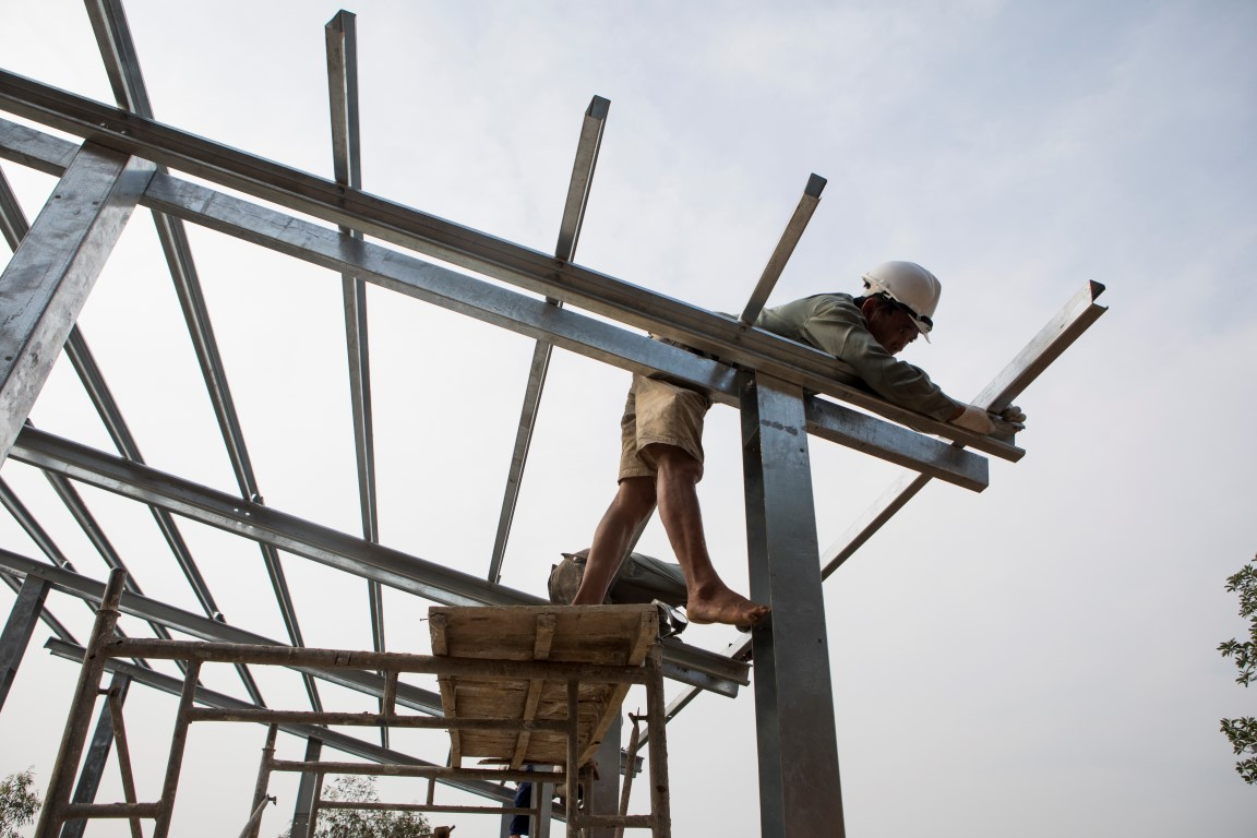 """Builders construct the frame of an """"S House,"""" designed by architect Vo Trong Nghia, in Hanoi, Vietnam, on April 20, 2017. Nghia plans to mass-manufacture the easy-to-assemble design for people in slums, remote areas or refugee camps around the world for the starting price of $1,500. (Amanda Mustard/The New York Times)"""