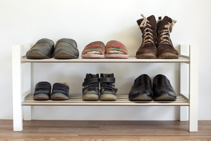 Six pairs of shoes on a shelf in the hallway in the house for the whole family: dad's mama's and child.