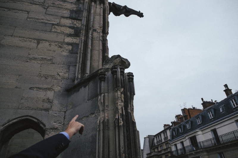 """André Finot, spokesman of the Notre Dame Cathedral in Paris, points out eroded masonry on the structure, Sept. 19, 2017. Rain, wind and pollution have battered the cathedral, which is seeking funds in France and in the United States to help pay for extensive renovations. """"Everywhere the stone is eroded, and the more the wind blows, the more all of these little pieces keep falling,"""" he said. (Dmitry Kostyukov/The New York Times)"""