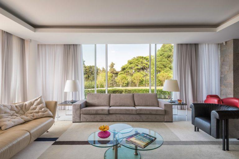 Mesa com três tampos em vidro é destaque desse living. Foto: Fernando Zequinão
