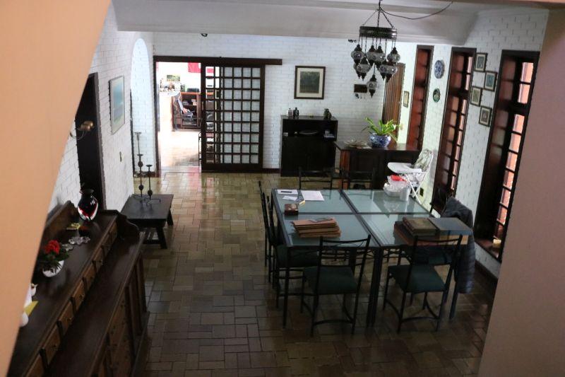 Nas salas, alguns dos destaques são as mesas de vidro, o jogo de mesa de jantar de Imbuia com dez cadeiras e dois aparadores, lustres e uma estante em módulos para montar conforme o espaço disponível.