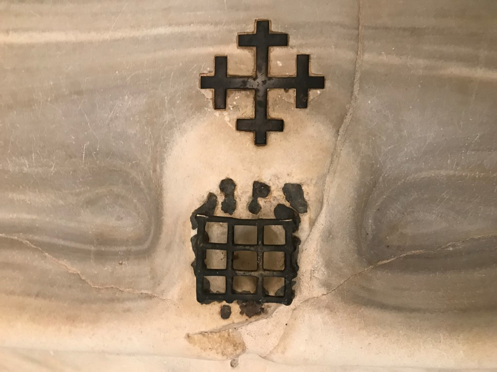 A medieval cross and grate set into the marble staircase which Catholic tradition holds Jesus climbed at his judgment before the Roman prefect Pontius Pilate, in Rome, April 8, 2019. The steps, now in a sanctuary across from the Basilica of St. John Lateran, were purportedly brought to Rome in 326 A.D.; the grate covers a spot said to be stained by a drop of Christ's blood. (Elisabetta Povoledo/The New York Times)