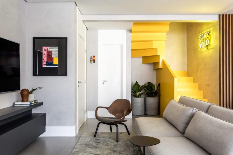 O contraste entre os tons amadeirados, o branco, o cinza e o amarelo da escada cria uma composição equilibrada no apartamento Pipa, de Giuliano Marchiorato. Fotos: Eduardo Macarios / Divulgação