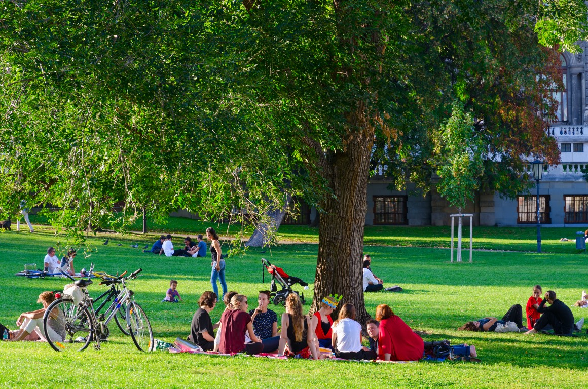 VIENNA, AUSTRIA - SEPTEMBER 17, 2018: Company of young people is resting in popular public Burggarten park on sunny September day, Vienna, Austria