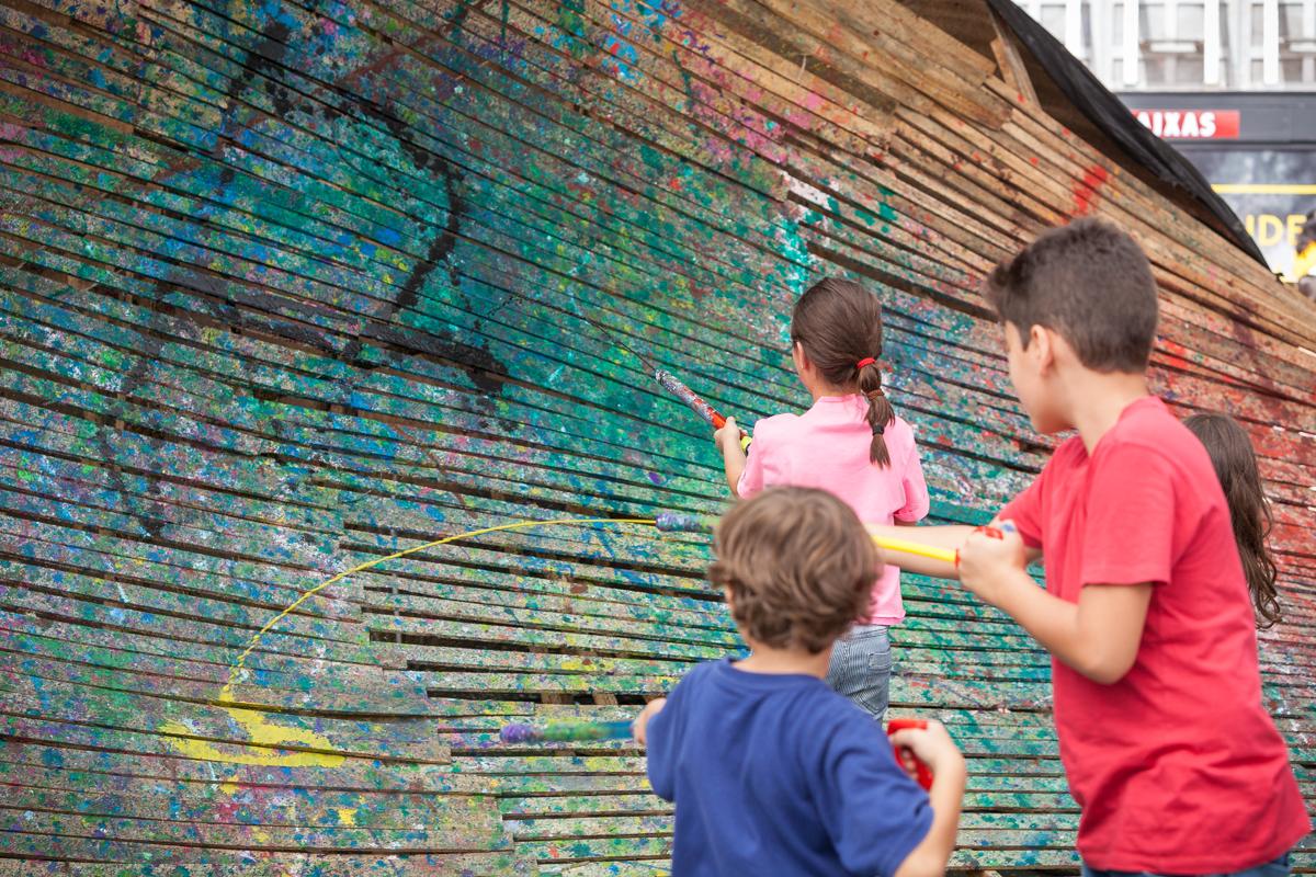 Crianças utilizam armas de plástico coloridas para pintar estrutura de madeira concebida como uma onda pelo artista plástico Tony Reis. Fotos: Fernando Zequinão/Gazeta do Povo