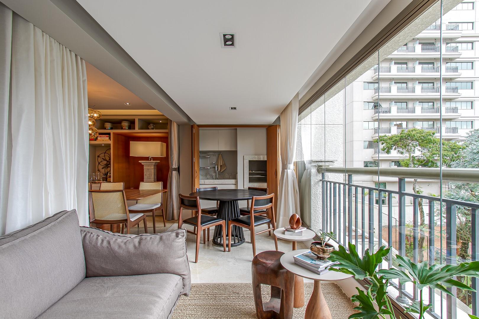 Na varanda, bancada e churrasqueira são integradas à parte social do apartamento, mas podem ser isoladas pelos painéis articulados que as escondem quando não utilizadas. Foto: Francis Larsen / Divulgação
