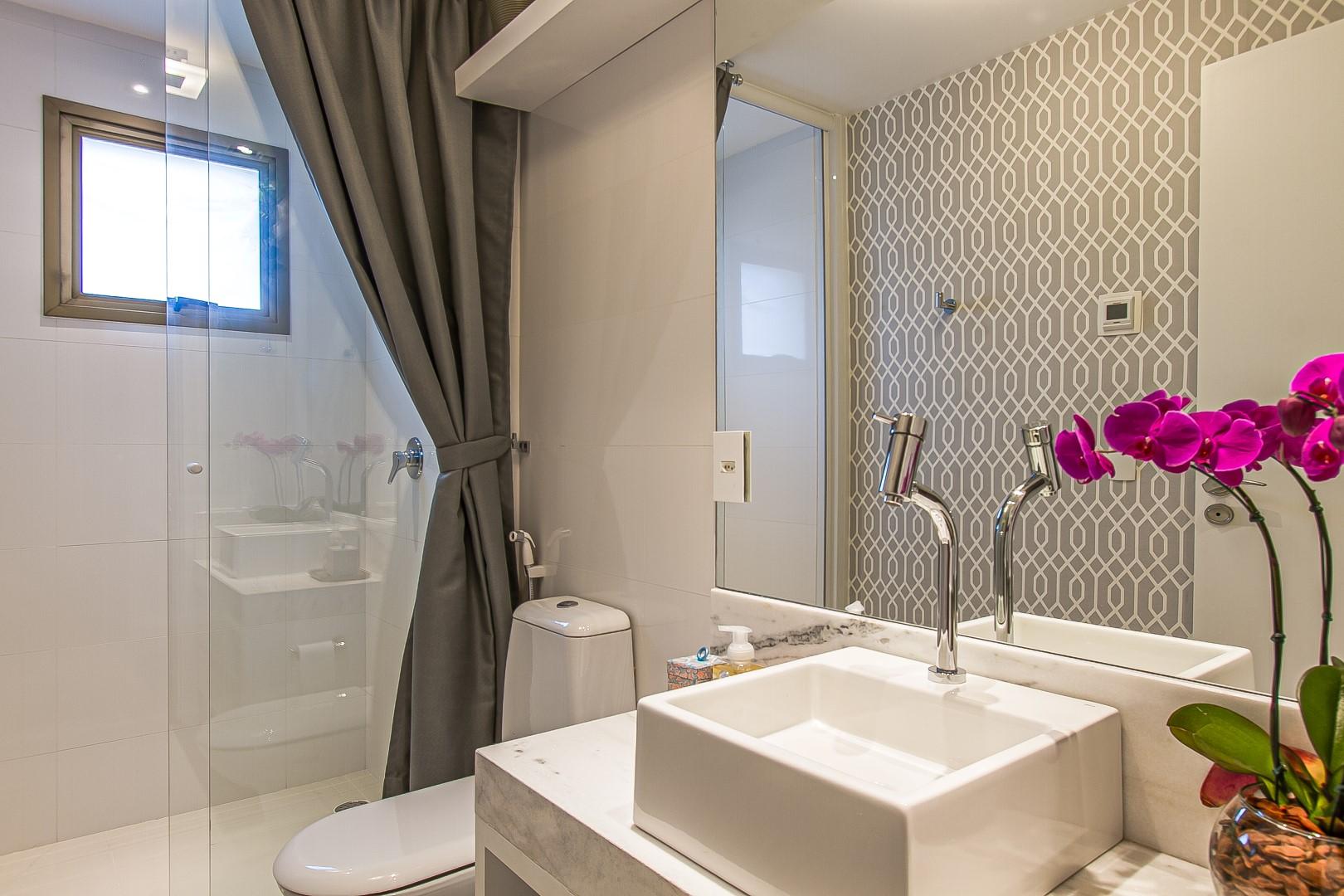 Os banheiros na suíte trazem revestimentos iguais, mas são diferenciados pelos acabamentos de metal, cromados para ela e em preto fosco para ele. Foto: Francis Larsen / Divulgação