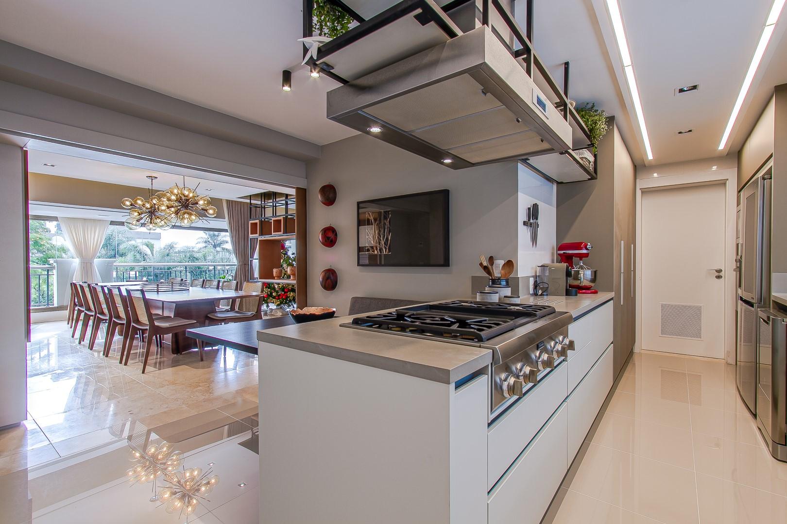 Cozinha é integrada ao restante das áreas comuns, mas pode ser isolada por meio de painéis instalados entre os cômodos. Foto: Francis Larsen / Divulgação
