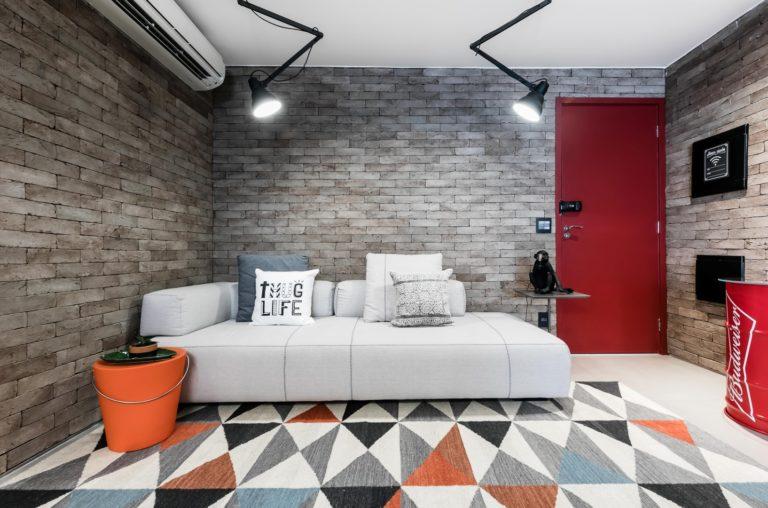 Atmosfera de pub moderno é garantida pela escolha dos materiais e tonalidades no projeto de Luiz Paulo Andrade. Destaque para a porta vermelha. Foto: Aphograph / Divulgação