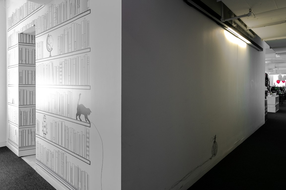 A door in the center of a mural of bookshelves opens inward to a secret library room, at Shutterstock in New York, Aug. 9, 2019. Secret rooms are popping up in workplaces. (Jeenah Moon/The New York Times)