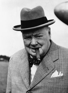 02 Sep 1949, London, England, UK --- British statesman Winston Churchill in 1949, smoking one of his beloved cigars as he leaves the plane that brought him back from a continental holiday. He caught cold while swimming on the Riviera, but soon recovered. --- Image by © Bettmann/CORBIS