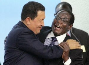 (FILES) This photo taken October 17, 2005 shows Venezuelan President Hugo Chavez (L) hugging Zimbabwe's President Robert Mugabe (R) after Mugabe's speech during a hunger conference to mark the 60th anniversary of the United Nation's Food and Agriculture Organisation at Rome's FAO headquarters. An official in Mugabe's ZANU-PF party said April 1, 2008 that Mugabe, who has ruled the former British colony since independence in 1980, is ready to step down after he accepted he failed to win the country's presidential election. The 84-year-old Mugabe, Africa's oldest leader, has blamed the economic woes on the European Union and the United States, which imposed sanctions on his inner circle after he was accused of rigging his 2002 re-election. AFP PHOTO / GIULIO NAPOLITANO (Photo credit should read GIULIO NAPOLITANO/AFP/Getty Images)