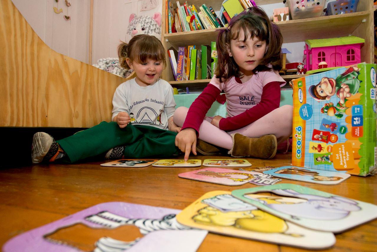 Os quebra-cabeças são diversão garantida para as irmãs Isis, 2 anos, e Lara, 6, quando elas não estão  brincando no quintal. Foto: Hugo Harada/Gazeta do Povo