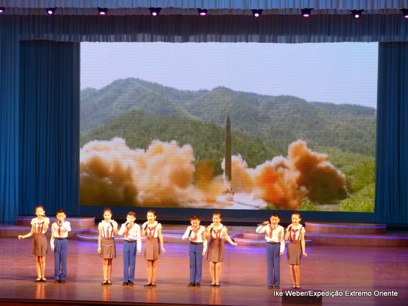 Na apresentação para turistas, a propaganda do poderio bélico da Coreia do Norte é exibida com crianças cantando em homenagem ao partido comunista. Foto: Ike Weber/acervo pessoal.