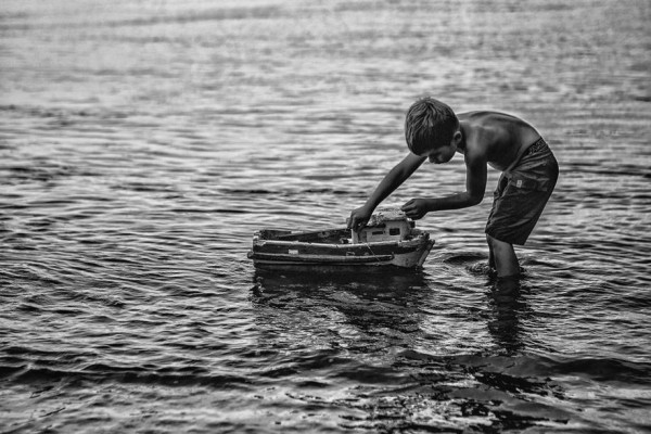 Criança brinca com barquinho nos arredores de Superagüi. Foto: Jonathan Campos/Gazeta do Povo