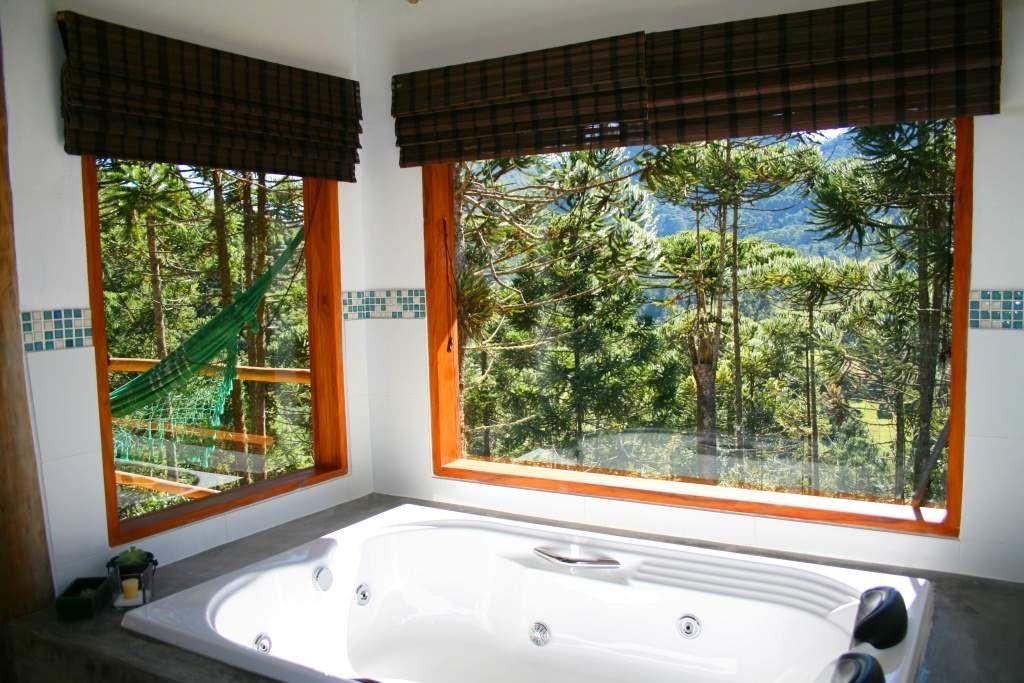A hidromassagem dupla é rodeada por grandes janelas de vidro. O que garante a privacidade é a vista para a floresta de araucárias. Foto: Jefferson Renó/Pousada Casa Campestre.