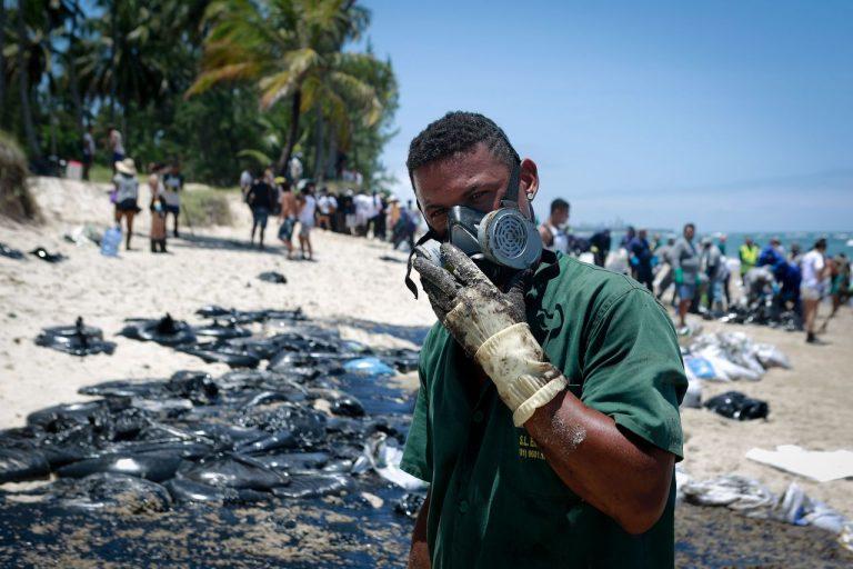 Contato prolongado com substância tem risco de câncer. Cartilha faz alerta de cuidados para voluntários que auxiliam na limpeza das praias. Foto: Leo Malafaia / AFP.