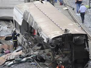 Rescue workers stand amongst wreckage of a train crash near Santiago de Compostela