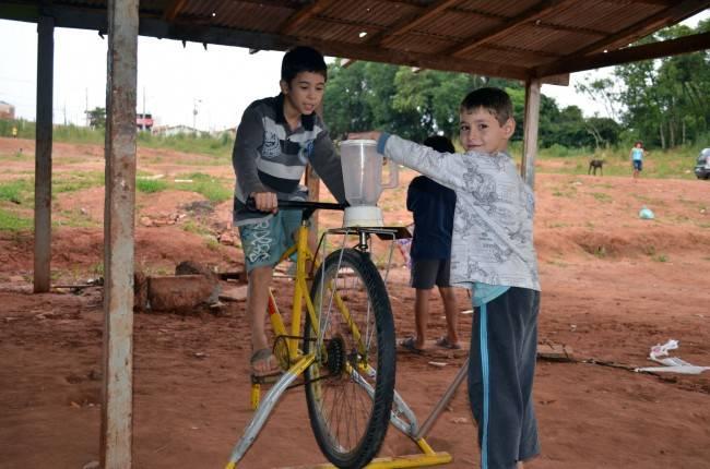 Crianças da comunidade Nova Primavera brincam na bicimáquina liquadora. (Foto: ACN/Ir e Vir de Bike)