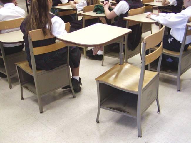 Carteira vazia em meio à sala de aula cheia