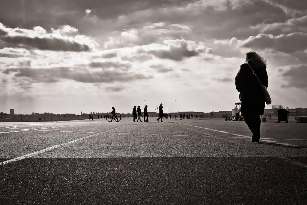 Uma foto em preto e branco de uma mulher andando sozinha.