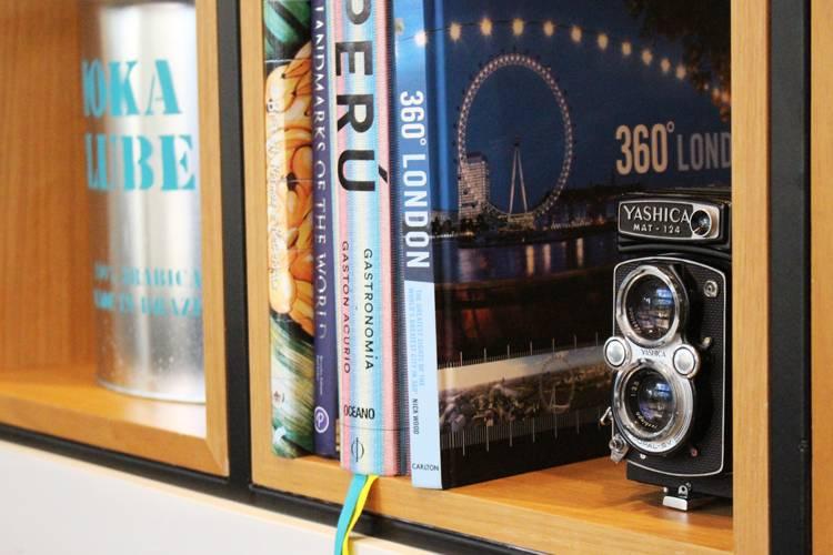 Cookie Stories por Lorenzo Bernardi Estante com livros e câmeras fotográficas