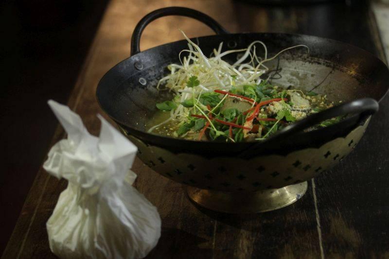 O curry vermelho com amendoim e tofu frito é servido na mini wok. Ao lado, o arroz thai em papel vegetal. Foto: Apneia Filmes/Divulgação