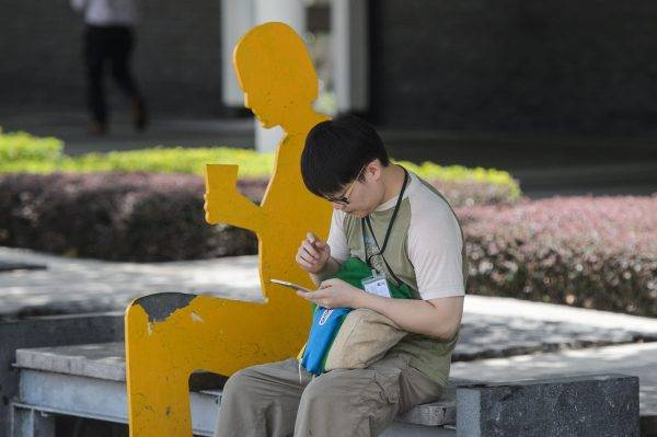 A woman uses her phone to play the Pokemon Go app in the Central district of Hong Kong on July 26, 2016.  The Chinese army garrisoned in Hong Kong has warned people searching for Pikachu and other virtual monsters to stay off their premises, as Pokemon Go mania sweeps the smartpho ne-obsessed city. / AFP PHOTO / Anthony WALLACE
