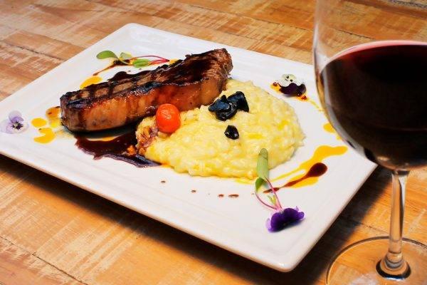 Bife de chorizo com molho demi glace, acompanhado de risoto com queijo gruyère e alho negro - a carne nobre no jantar harmonizado da Devons Steak House. (Fotos/ Black Flag Publicidade)