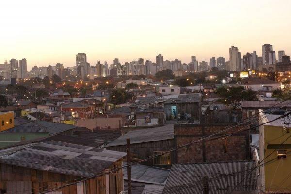 Contraste de renda: comunidade pobre em Curitiba com prédios de padrão mais alto ao fundo. Foto: Marcelo Andrade/Gazeta do Povo