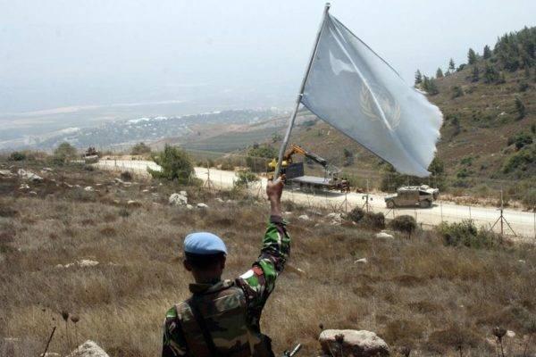 Membro da ONU acena uma bandeira da Força Interina das Nações Unidas no Líbano (UNIFIL)   em 2010