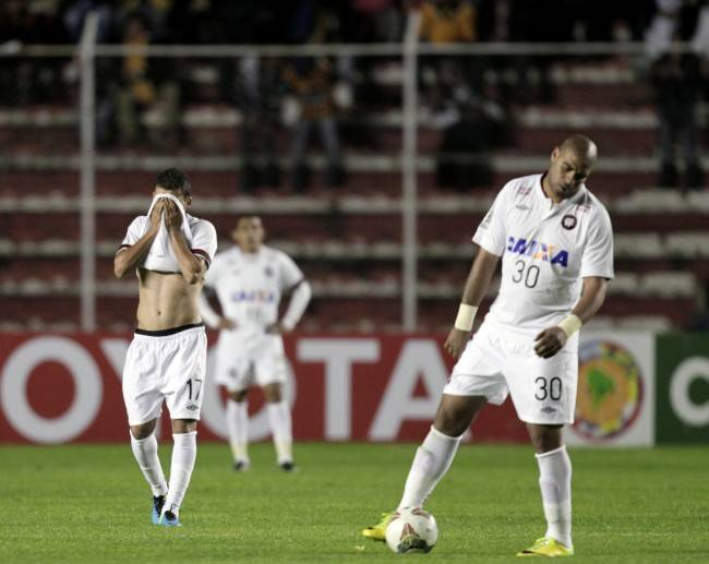 Adriano and teammate Paulo Dias of Brazil's Atletico Paranaense react after Bolivia's The Strongest scored their second goal during their Copa Libertadores soccer match in La Paz