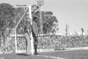 Atletiba de 1974. Jairo ouve instruções. Ao fundo, torcida coxa abarrota a reta do relógio da Vila Capanema.